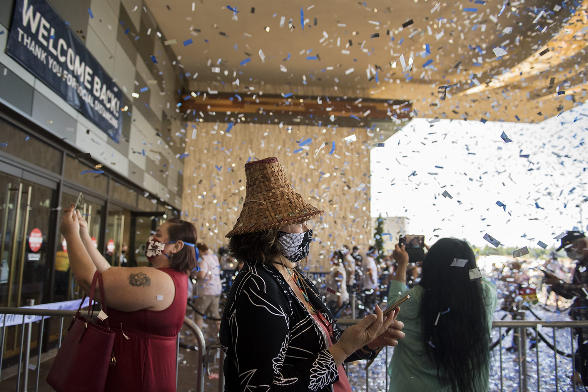 Katherine Vasquez, a Cowlitz Tribe councilwoman who lives Lacey, center, is surrounded by confetti as she celebrates the reopening of ilani Casino Resort with members of the public on Thursday morning, May 28, 2020. The casino has been closed for 70 days due to the COVID-19 pandemic. All guests are required to have their temperature checked upon arrival and to wear a mask. (Amanda Cowan/The Columbian)