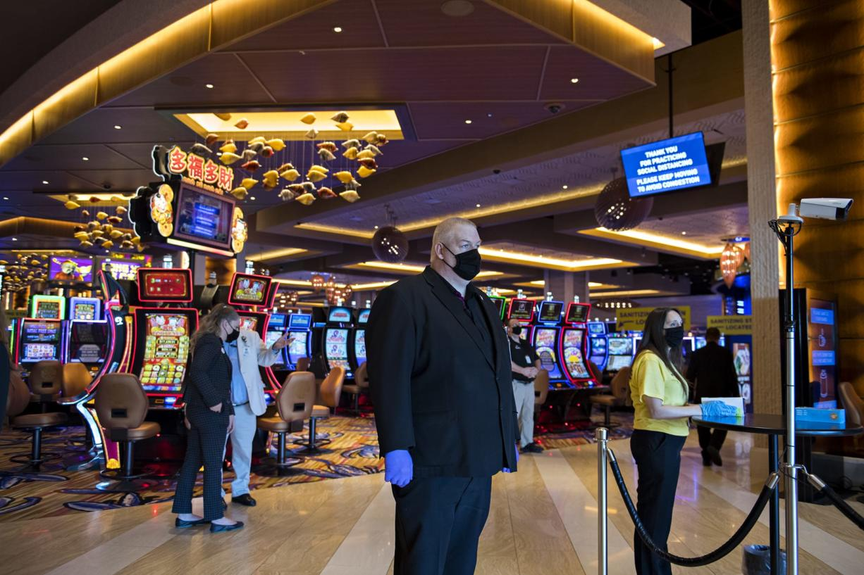 Security officer Stephen Henderson, center, wears a mask and gloves as he keeps an eye on the reopening while a thermometer, right, measures the temperature of guests at ilani Casino Resort on Thursday morning, May 28, 2020.