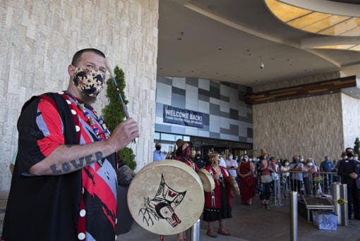 Jeramiah Wallace of the Cowlitz Drum Group, left, keeps the beat while celebrating the reopening of ilani Casino Resort with the crowd on Thursday morning, May 28, 2020.