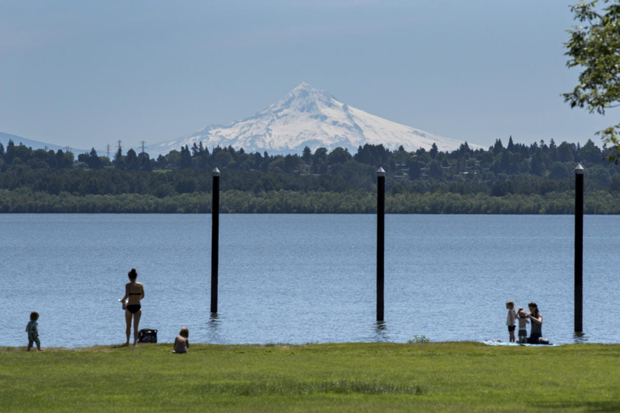 Visitors to Vancouver Lake take in the sunshine and a snow-capped view of Mount Hood while enjoying the day and keeping their distance on Wednesday. The temperature reached 80 degrees Wednesday and will continue to climb today.
