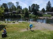 People line the beach on the first day of official reopening at Sandy Swimming Hole Park in Washougal on Friday. The park has been closed due to the COVID-19 public health emergency.