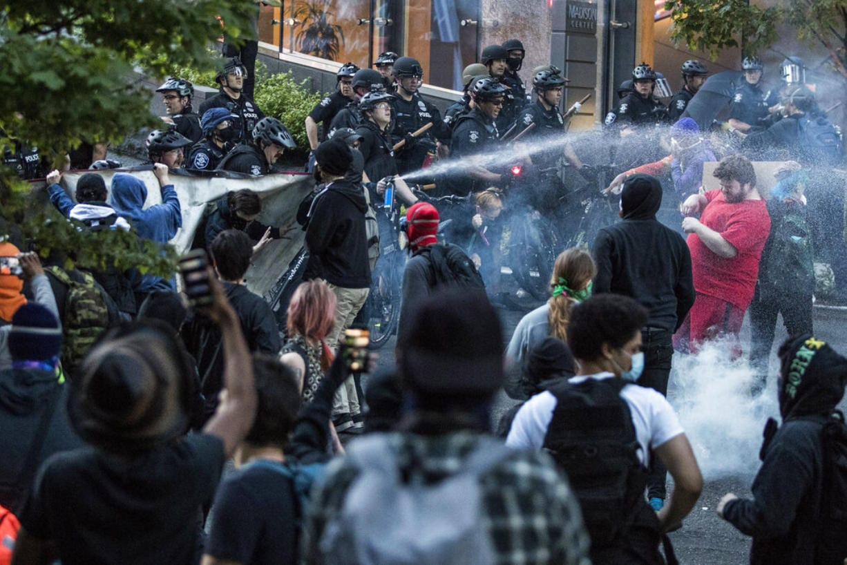 In this May 29, 2020, photo, police push back demonstrators after objects were thrown at them at 5th Avenue and Madison Street during a march in solidarity with Minneapolis and protesting police brutality in Seattle. Protests have been erupting all over the country after George Floyd died earlier this week in police custody in Minneapolis.