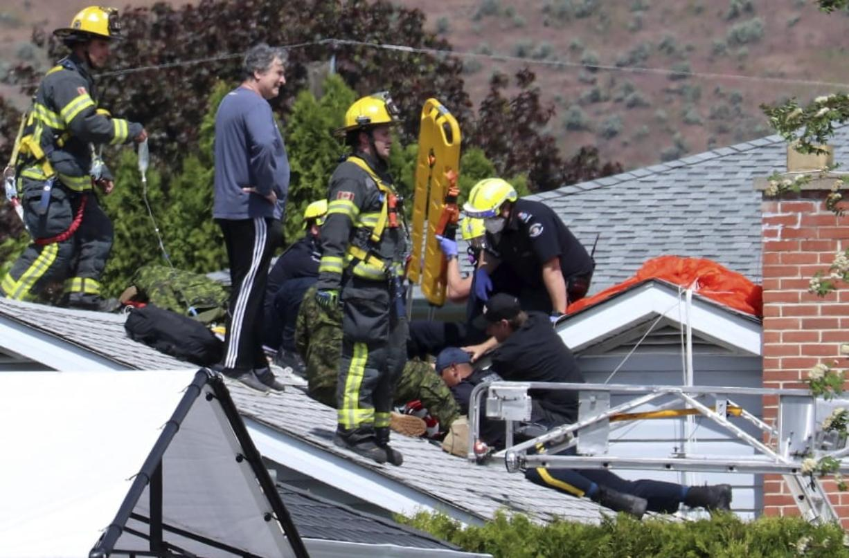 First responders attend to a person on a rooftop at the scene of a crash involving a Canadian Forces Snowbirds airplane in Kamloops, British Columbia, Sunday, May 17, 2020.