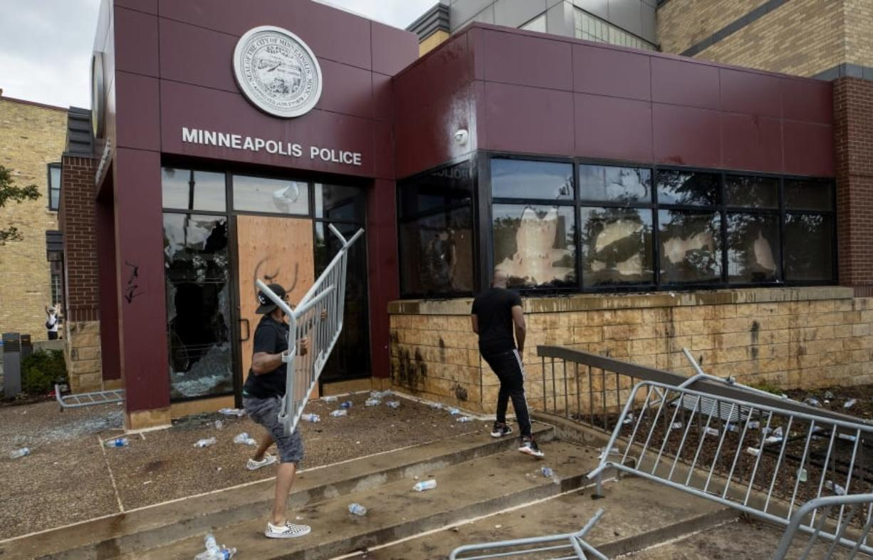 Protesters damage properties at the Minneapolis 3rd Police Precinct in Minneapolis on Wednesday, May 27, 2020. The mayor of Minneapolis called Wednesday for criminal charges against the white police officer seen on video kneeling against the neck of a handcuffed black man who complained that he could not breathe and died in police custody.