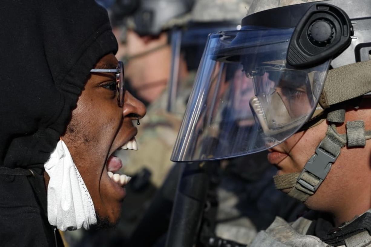 Protesters and National Guardsmen face off on East Lake Street, Friday, May 29, 2020, in St. Paul, Minn. Protests continued following the death of George Floyd, who died after being restrained by Minneapolis police officers on Memorial Day.