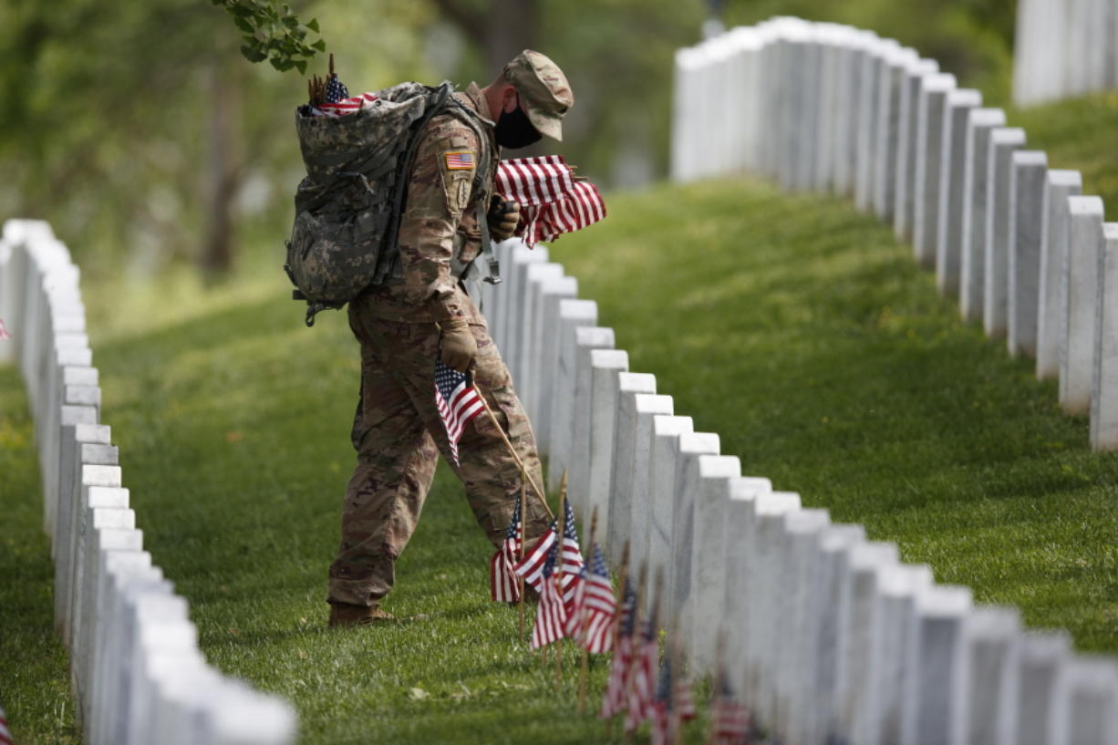 """A member of the 3rd U.S. Infantry Regiment also known as The Old Guard, wears a face mask as he places flags in front of each headstone for """"Flags-In"""" at Arlington National Cemetery in Arlington, Va., Thursday, May 21, 2020, to honor the Nation's fallen military heroes ahead of Memorial Day."""