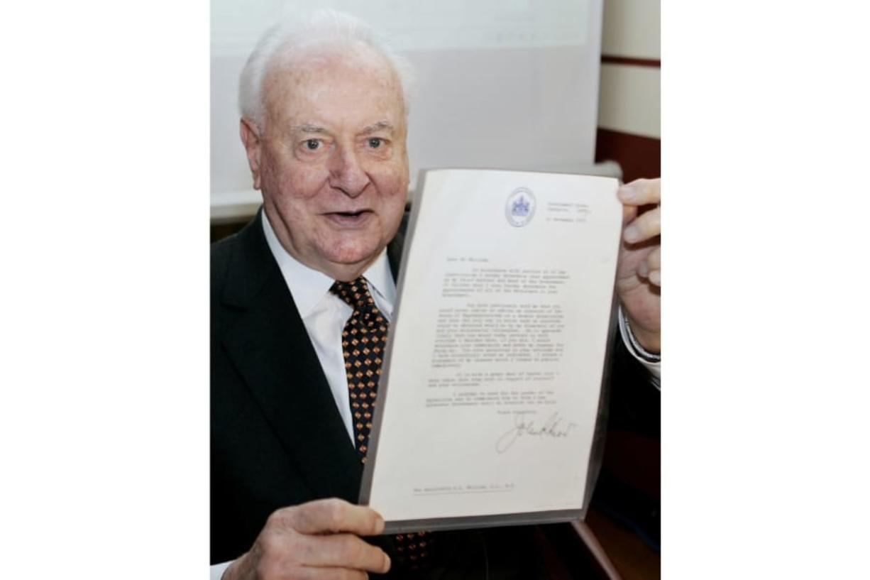 FILE - In this Nov. 7, 2005, file photo, former Australian Prime Minister Gough Whitlam holds up the original copy of his dismissal letter he received from then Governor-General Sir John Kerr on Nov. 11, 1975, at a book launch in Sydney, Australia. The High Court's majority decision in historian Jenny Hocking's appeal on Friday, May 29, 2020 overturned lower court rulings that more than 200 letters between the monarch of Britain and Australia and Governor-General Sir John Kerr before he dismissed Prime Minister Gough Whitlam's government were personal and might never be made public.