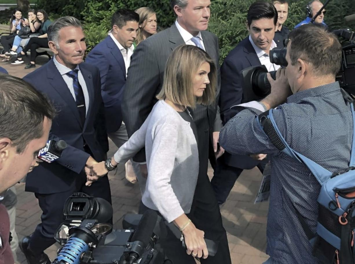 FILE - In this Aug. 27, 2019, file photo, Lori Loughlin departs federal court with her husband, clothing designer Mossimo Giannulli, left, in Boston, after a hearing in a nationwide college admissions bribery scandal. Loughlin and Giannulli have agreed to plead guilty in a video arraignment scheduled for Friday, May 22, 2020, to charges of trying to secure the fraudulent admission of their two children to the University of Southern California as purported athletic recruits.