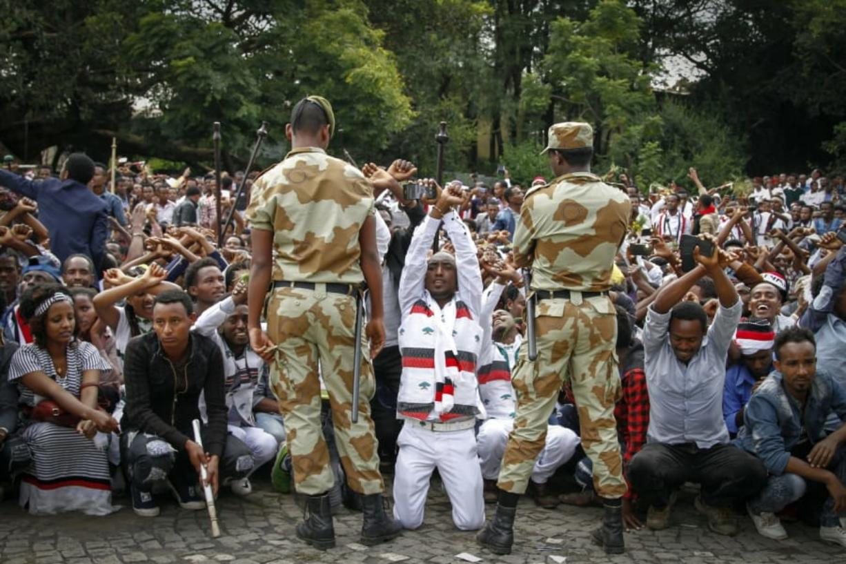 FILE - In this Sunday, Oct. 2, 2016 file photo, Ethiopian soldiers try to stop protesters in Bishoftu, during a declared state of emergency, in the Oromia region of Ethiopia. A new report by the rights group Amnesty International issued Friday, May 29, 2020 accuses Ethiopia's security forces of extrajudicial killings and mass detentions in the restive Oromia region even as the country's reformist prime minister was awarded the Nobel Peace Prize.