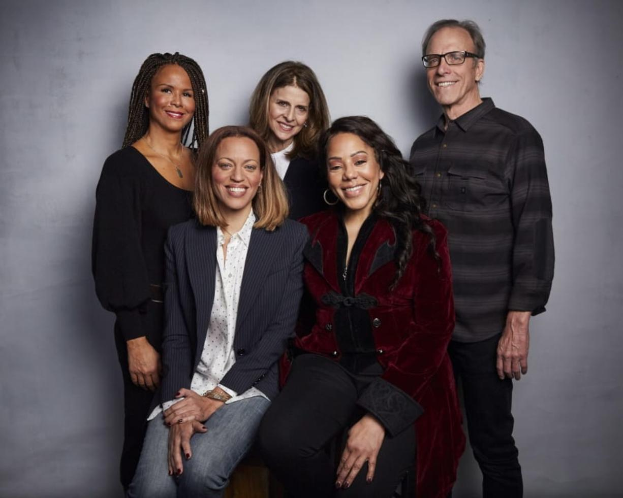 """FILE - In this Jan. 26, 2020 file photo, Sil Lai Abrams, back row from left, director Amy Ziering, director Kirby Dick, Drew Dixon, seated left, and Sheri Hines pose for a portrait to promote the film """"On the Record"""" at the Music Lodge during the Sundance Film Festival in Park City, Utah. The film provides an intimate portrayal of the agonizing process of calculating whether to go public with harassment and abuse claims."""