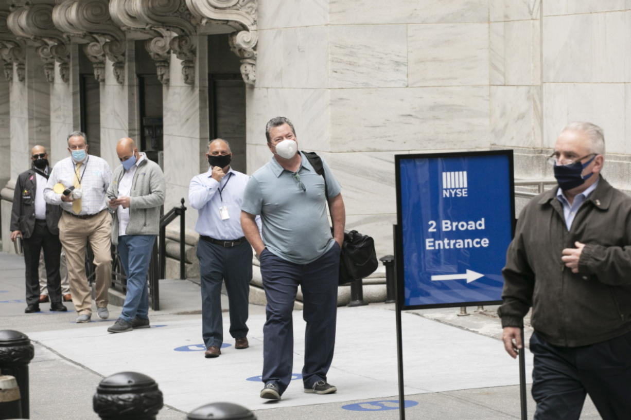 New York Stock Exchange employees wait to enter the building as the trading floor partially reopens, Tuesday, May 26, 2020.