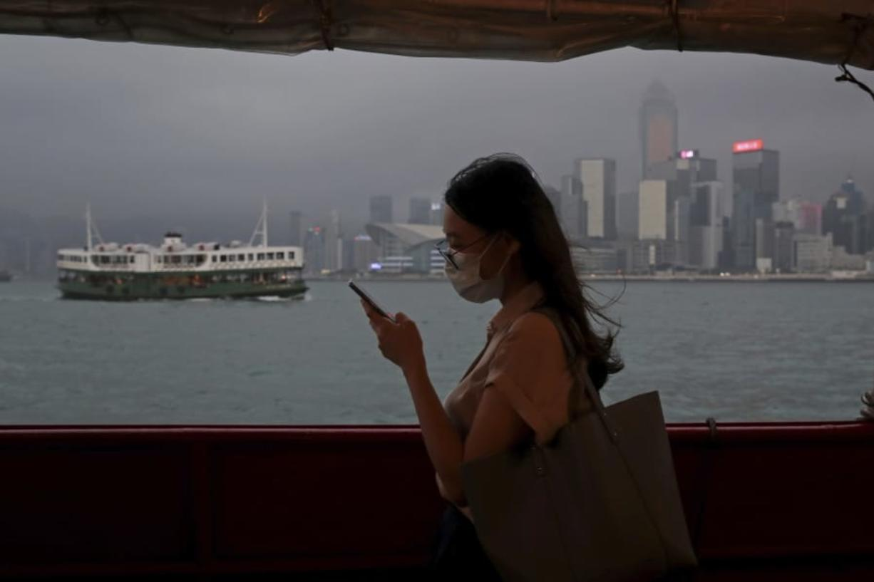 In this Thursday, May 28, 2020, photo, a woman uses a smartphone on a ferry in Hong Kong. Hong Kong has been living on borrowed time ever since the British made it a colony nearly 180 years ago, and all the more so after Beijing took control in 1997, granting it autonomous status. A national security law approved by China's legislature Thursday is a reminder that the city's special status is in the hands of Communist Party leaders who have spent decades building their own trade and financial centers to take Hong Kong's place.