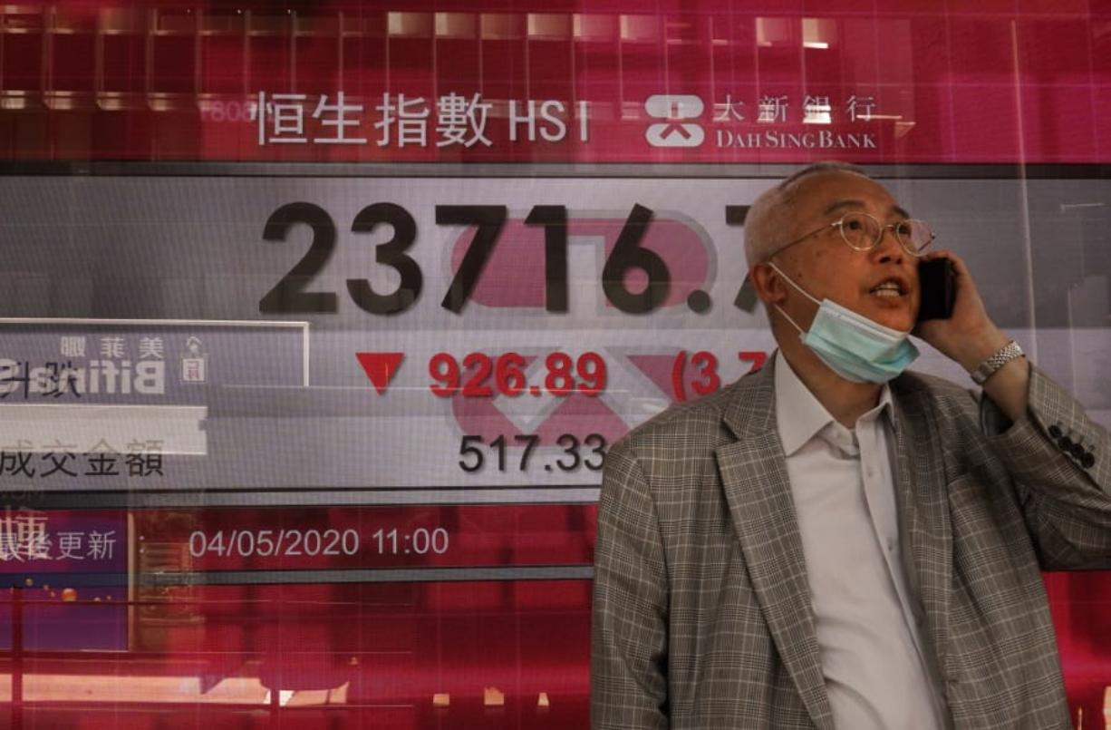 A man wearing face mask walks past a bank electronic board showing the Hong Kong share index at Hong Kong Stock Exchange Monday, May 4, 2020. Shares have skidded in Asia as tensions between the Trump administration and China over the origins and handling of the coronavirus pandemic rattle investors.
