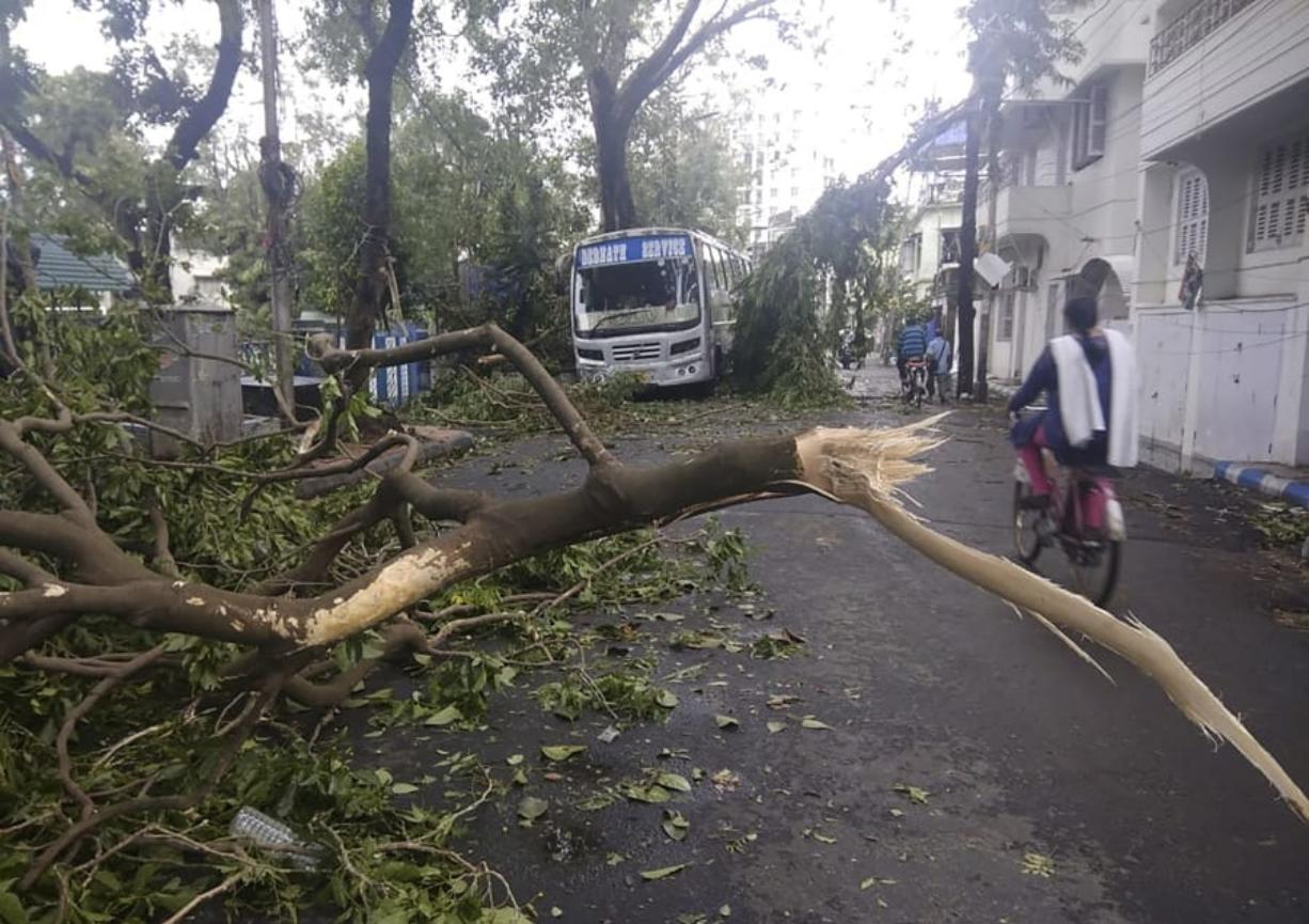 A girl rides a cycle past tree branches that fell after cyclone Amphan hit the region, in Kolkata, India, Thursday, May 21, 2020. A powerful cyclone that slammed into coastal India and Bangladesh has left damage difficult to assess Thursday.
