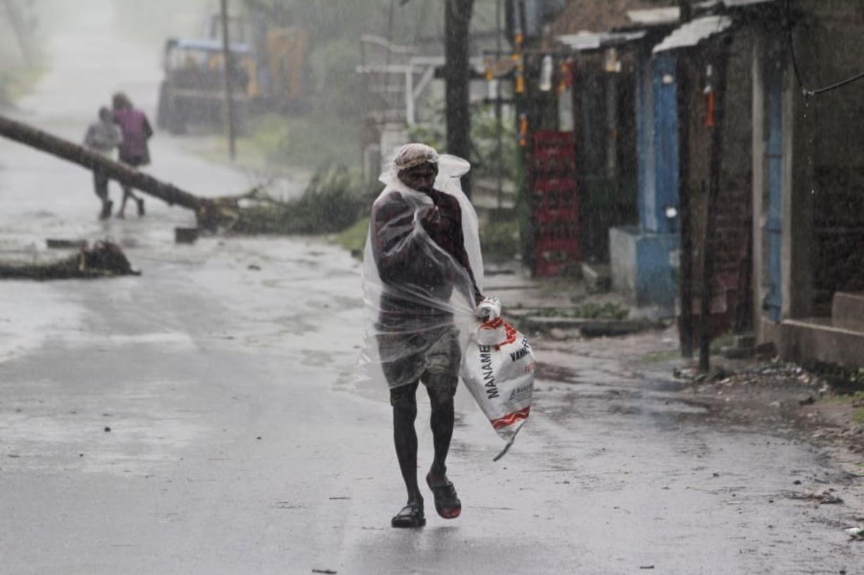 A man covers himself with a plastic sheet and walks in the rain ahead of Cyclone Amphan landfall, at Bhadrak district, in the eastern Indian state of Orissa, Wednesday, May 20, 2020. A strong cyclone blew heavy rains and strong winds into coastal India and Bangladesh on Wednesday after more than 2.6 million people were moved to shelters in a frantic evacuation made more challenging by coronavirus.