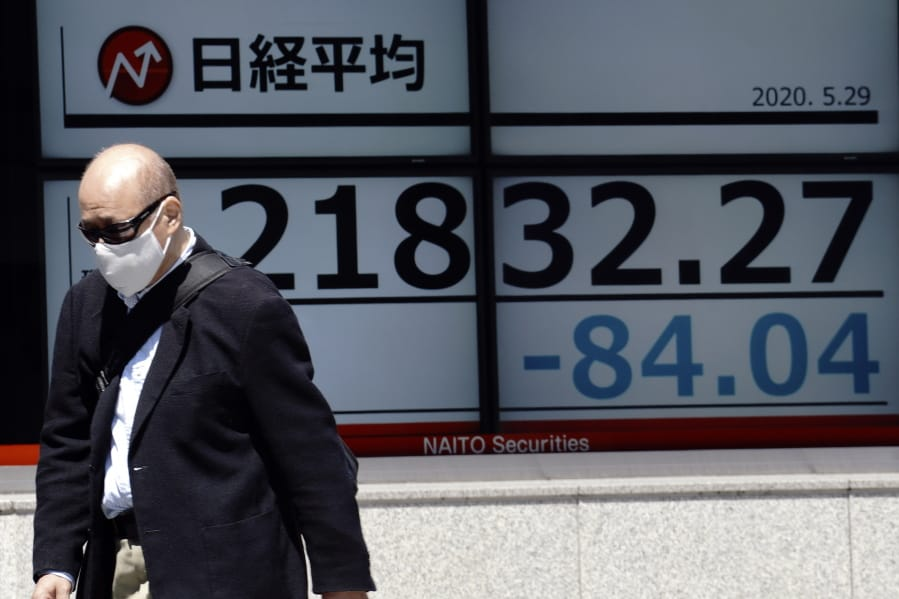 A man walks past an electronic stock board showing Japan's Nikkei 225 index at a securities firm in Tokyo Friday, May 29, 2020. Shares fell Friday in Asia after Wall Street's rally petered out amid worries about flaring U.S.-China tensions.