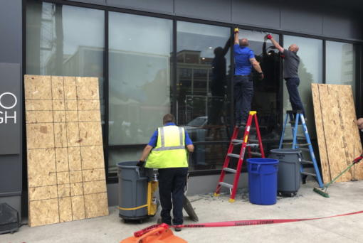 Workers repair smashed windows at a building south of downtown on Friday, May 29, 2020, in Columbus, Ohio. Multiple downtown storefronts had their windows smashed and some businesses were looted early Friday. The damage happened as protesters angry over the death of George Floyd in Minneapolis police custody turned out for a demonstration in Columbus that began peacefully but turned violent, with windows smashed at the Ohio Statehouse and storefronts along surrounding downtown streets.