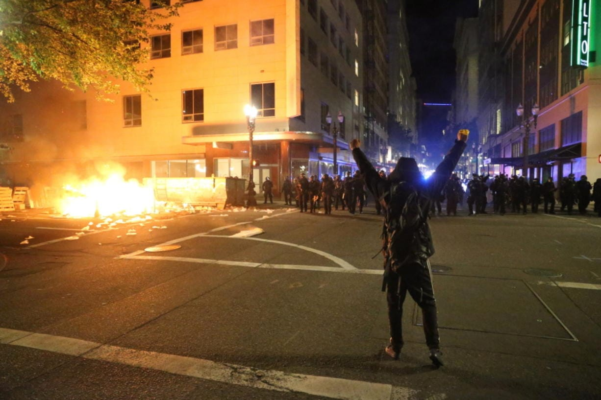 A protestor faces police officers in downtown in Portland, Friday.