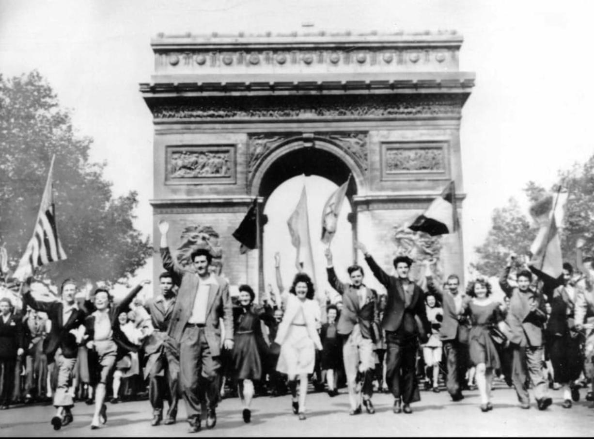 FILE - In this May 8, 1945 file photo Parisians march through the Arc de Triomphe jubilantly waving flags of the Allied Nations as they celebrate the end of World War II in Europe. Nazi commanders signed their surrender to Allied forces in a French schoolhouse 75 years ago this week, ending World War II in Europe and the Holocaust.