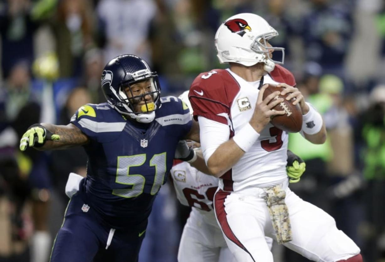 FILE - In this Nov. 15, 2015, file photo, Seattle Seahawks outside linebacker Bruce Irvin (51) pressures Arizona Cardinals quarterback Carson Palmer during the first half of an NFL football game in Seattle. Irvin is thrilled to be back where his NFL journey started. Irvin jumped at the chance to return to Seattle this offseason, but his reunion with the Seahawks comes with the expectation he can help a lackluster pass rush.