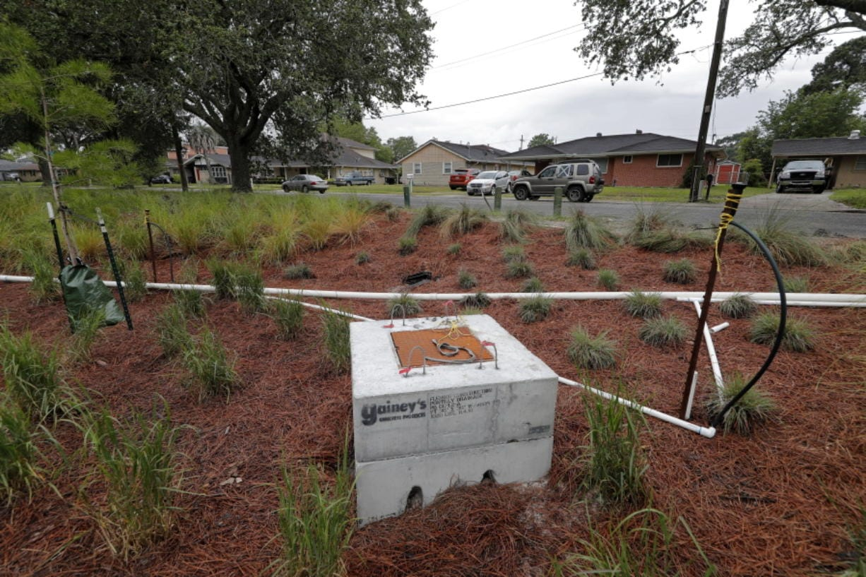 """In this Friday, May 15, 2020 photo, houses are seen near a recently completed """"bioswale"""" at Prentiss Ave. and Press Drive in New Orleans.  For more than a century, New Orleans has depended on canals and pumps to get rid of stormwater in a city that is largely below sea level. Now a city that expanded by filling in wetlands is spending $270 million to create spaces for stormwater, like the water garden on a 25-acre site provided by nuns who lived there before Hurricane Katrina. It's also installing underground holding tanks, porous pavement and other measures to reduce storm flooding and the stress on huge pumps built in the 1910s."""
