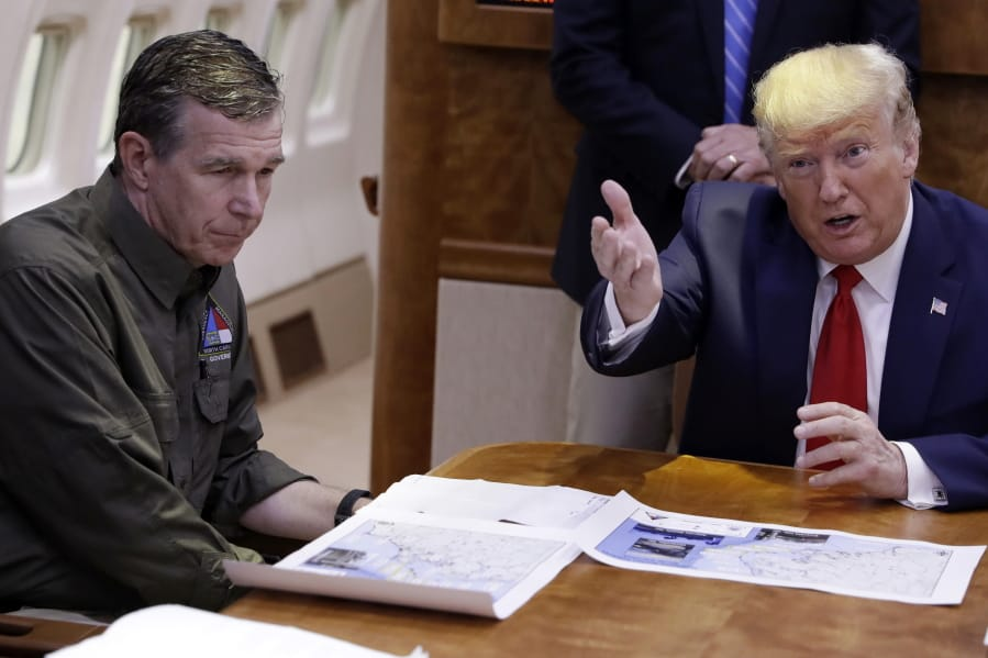 "FILE - In this Sept. 9, 2019, file photo, President Donald Trump participates in a briefing about Hurricane Dorian with North Carolina Gov. Roy Cooper, left, aboard Air Force One at Marine Corps Air Station Cherry Point in Havelock, N.C.  President Donald Trump demanded Monday, May 25, 2020, that North Carolina's Democratic governor sign off ""immediately"" on allowing the Republican National Convention to move forward in August with full attendance despite the ongoing COVID-19 pandemic."