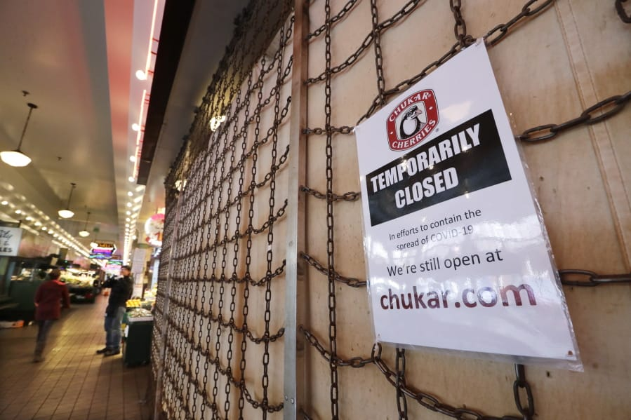 A sign explains the closure of a shop in the Pike Place Market in Seattle.