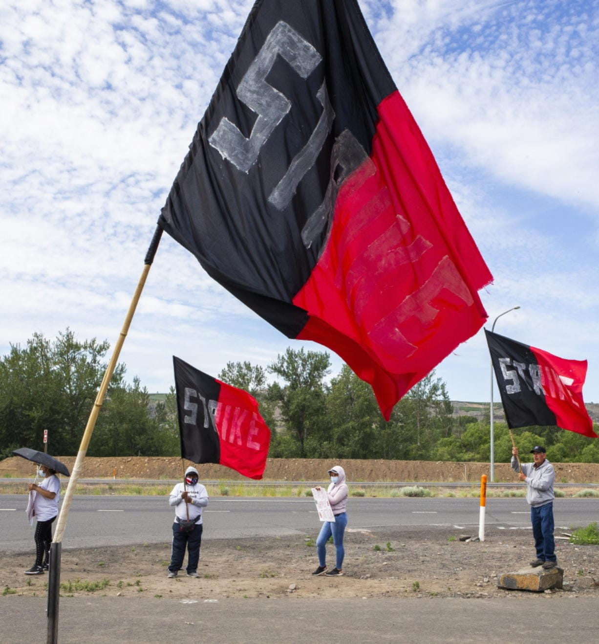 Allan Bros. workers protest along U.S. 12 shortly before coming to an agreement to return to work, Thursday, May 28, 2020, in Naches, Wash., after striking in protest of what they consider unsafe working conditions at several fruit warehouses during the COVID-19 outbreak.