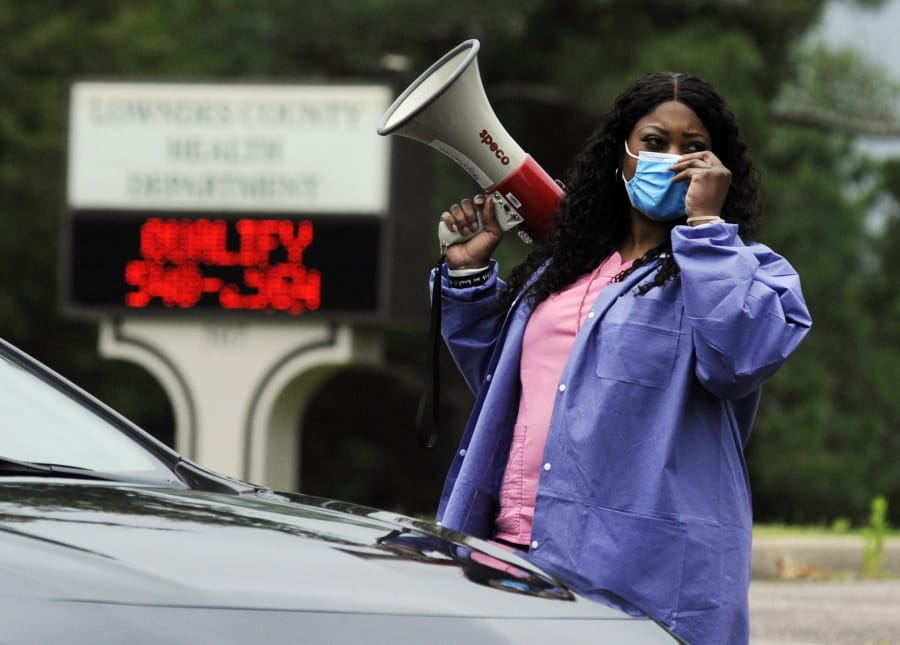 "In this May 27, 2020, photo, health care worker Tonya Wilkes adjusts her mask while working at a Lowndes County coronavirus testing site in Hayneville, Ala. Experts say Lowndes County and nearby poor, mostly black counties in rural Alabama are now facing a ""perfect storm"" as infections tick up: a lack of access to medical care combined with poverty and the attendant health problems that can worsen the outcomes for those who become sick."