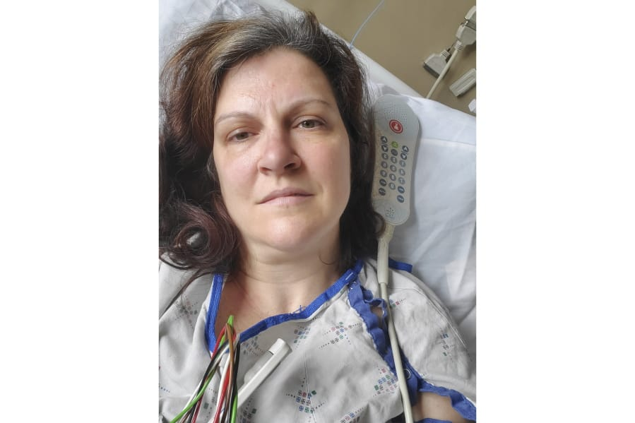 """This May 6, 2020 photo provided by Darlene Gildersleeve, 43, of Hopkinton, N.H. shows her at a Manchester, N.H. hospital. Gildersleeve thought she had recovered from COVID-19. Doctors said she just needed rest. And for several days, no one suspected her worsening symptoms were related -- until a May 4 video call, when her physician heard her slurred speech and consulted a specialist. """"You've had two strokes,'' a neurologist told her at the hospital."""