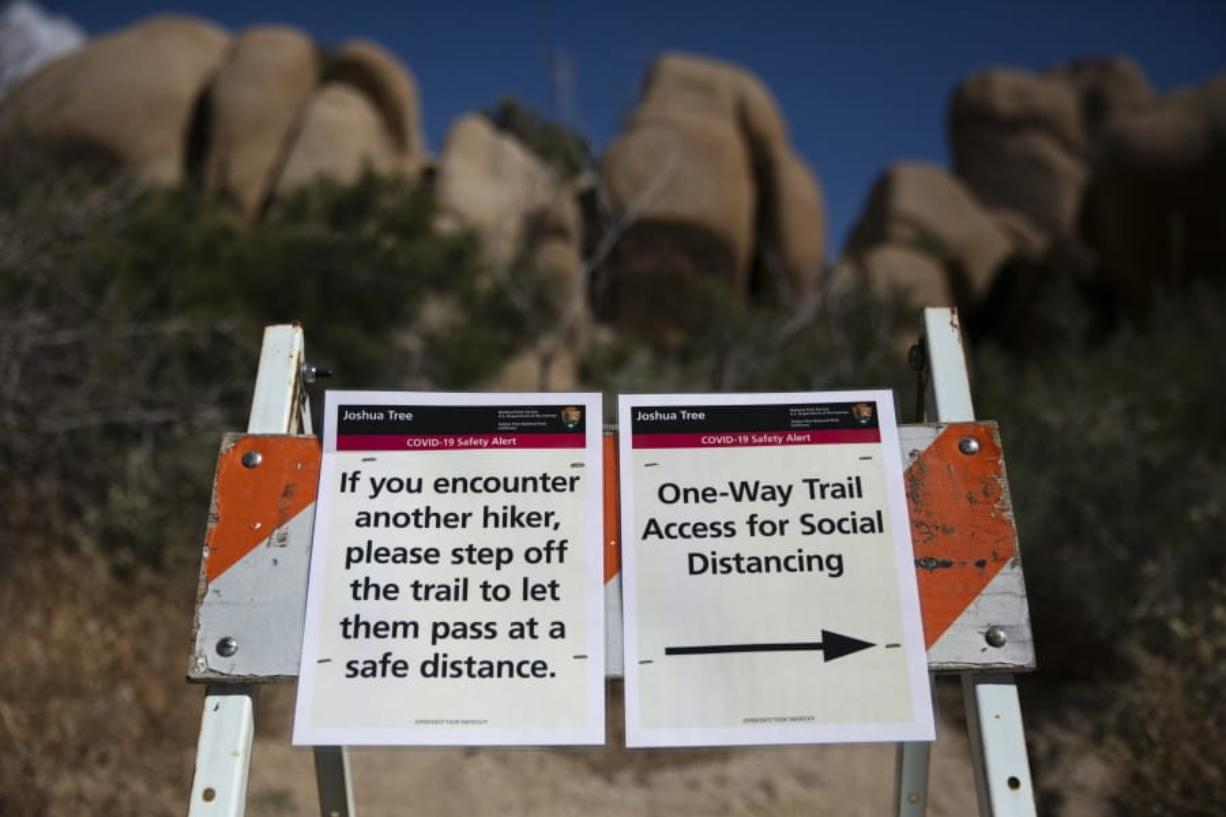 Signs advise visitors to social distance at Joshua Tree National Park in California, Tuesday, May 19, 2020. The park reopened this week after a lengthy closure to help slow the spread of the new coronavirus. (AP Photo/Jae C.