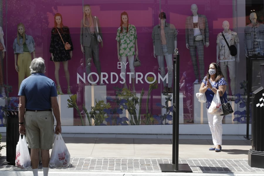Shoppers walks past a Nordstrom window display at The Grove shopping center Wednesday, May 27, 2020, in Los Angeles. California moved to further relax its coronavirus restrictions and help the battered economy. Retail stores, including those at shopping malls, can open at 50% capacity.