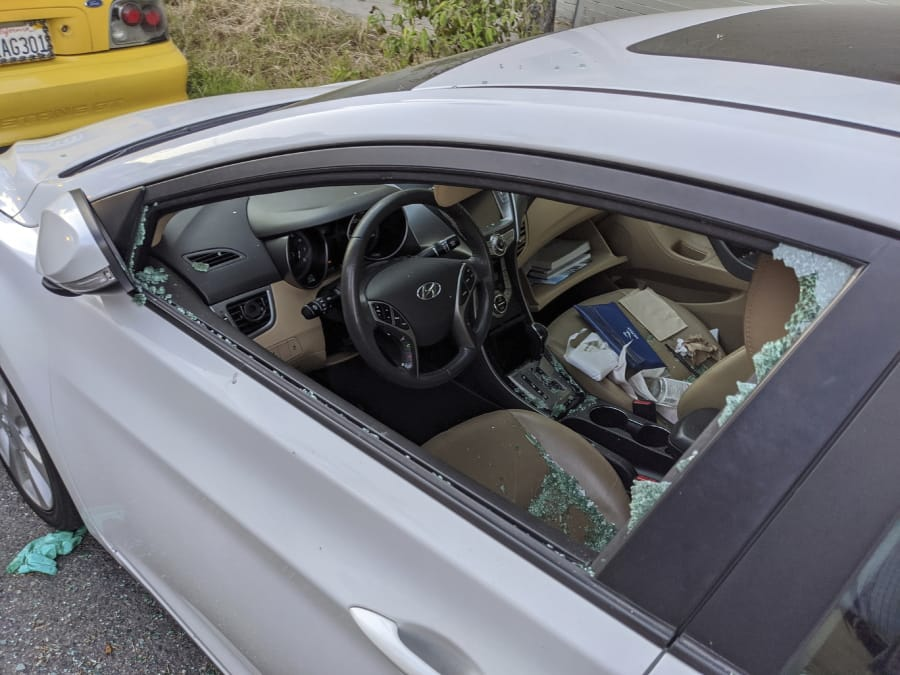 This Thursday, May 21, 2020, photo shows a parked car with a broken driver's side window after a smash-and-grab break-in in Los Angeles. The coronavirus hasn't been kind to car owners. With more people than ever staying home to lessen the spread of COVID-19, their sedans, pickup trucks and SUVs are parked unattended on the streets, making them easy targets for opportunistic thieves.
