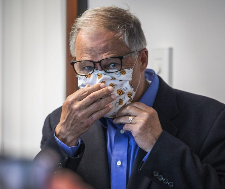Washington Gov. Jay Inslee puts on his face mask after speaking to the media, Wednesday, May 20, 2020, in Tumwater, Wash., about the state's effort at contact tracing amid the coronavirus pandemic.
