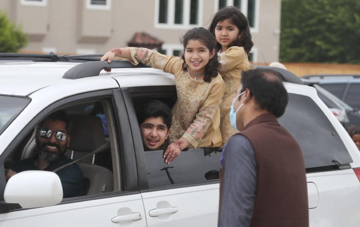 A family looks out from their vehicle during an Eid al-Fitr drive through celebration outside a closed mosque in Plano, Texas, Sunday, May 24, 2020. Many Muslims in America are navigating balancing religious and social rituals with concerns over the virus as they look for ways to capture the Eid spirit this weekend.