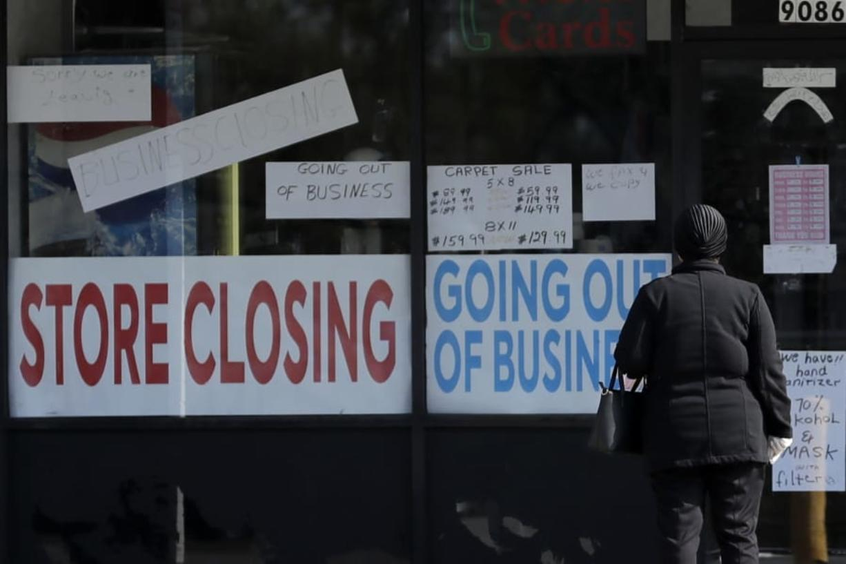 A woman looks at signs at a store closed due to COVID-19 in Niles, Ill., Wednesday, May 13, 2020. (AP Photo/Nam Y.