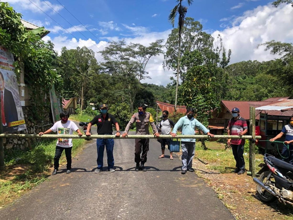 In this April 24, 2020, photo, provided by the Indigenous People Alliance of the Archipelago, indigenous peoples from the Buntao' community in Indonesia's North Toraja regency in South Sulawesi Province use a wooden barrier to block off their village. Indigenous peoples across the archipelago are locking down their villages in an effort to protect their communities from the coronavirus.