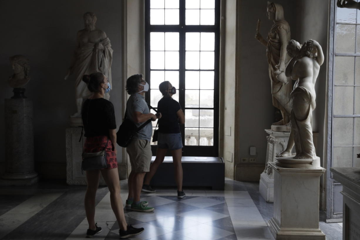 """Visitors wearing a face masks to prevent the spread of COVID-19 admire statues in the Rome Capitoline Museums, including the second century A.D. Roman marble statue """"Cupid and Psyche"""", at right, Tuesday, May 19, 2020. In Italy, museums were allowed to reopen this week for the first time since early March, but few were able to receive visitors immediately as management continued working to implement social distancing and hygiene measures, as well as reservation systems to stagger visits to museums in the onetime epicenter of the European pandemic."""