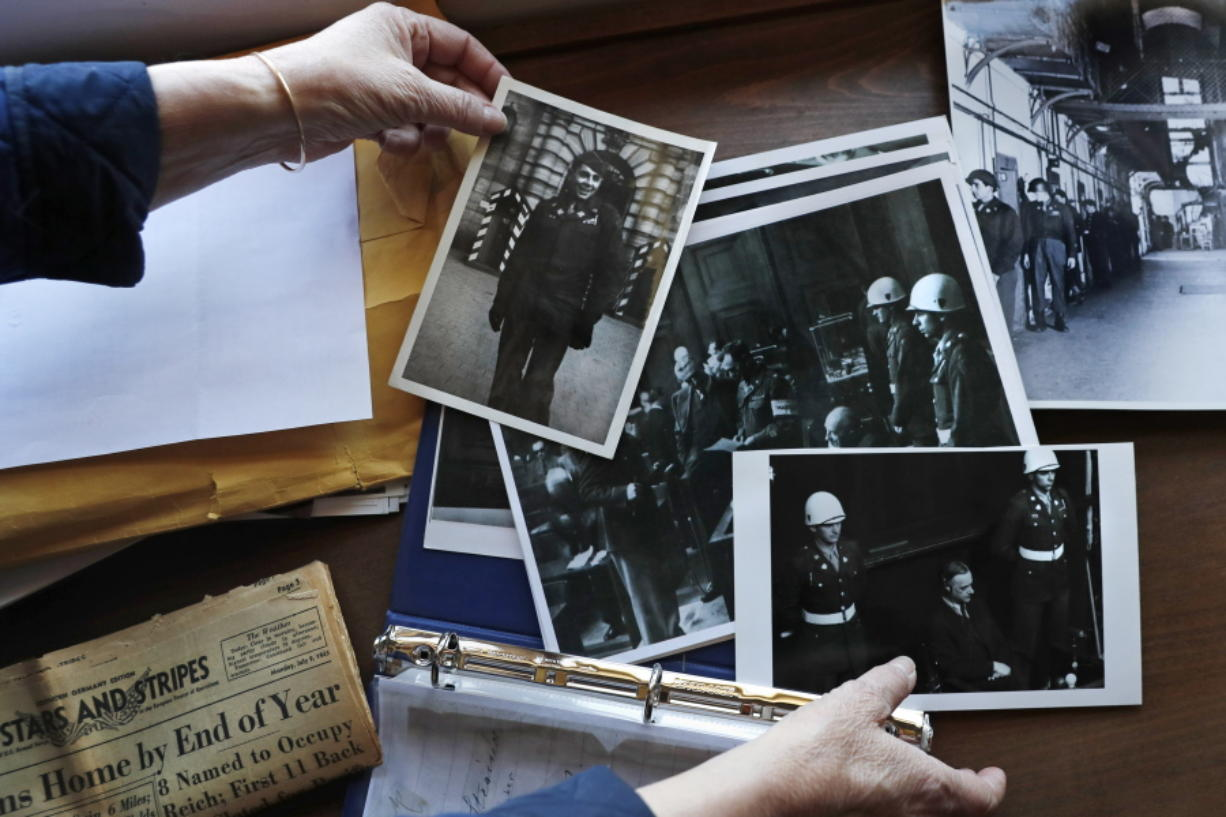 Emily DiPalma Aho looks over photographs and memorabilia of her father, Emilio DiPalma, a World War II veteran, at her home in Jaffrey, N.H., Wednesday, May 13, 2020. Emilio, who as a 19-year-old U.S. Army infantryman stood guard at the Nuremberg Nazi war crimes trials, died last month at the age of 93 after contracting the coronavirus at Holyoke Soldiers' Home in Massachusetts.