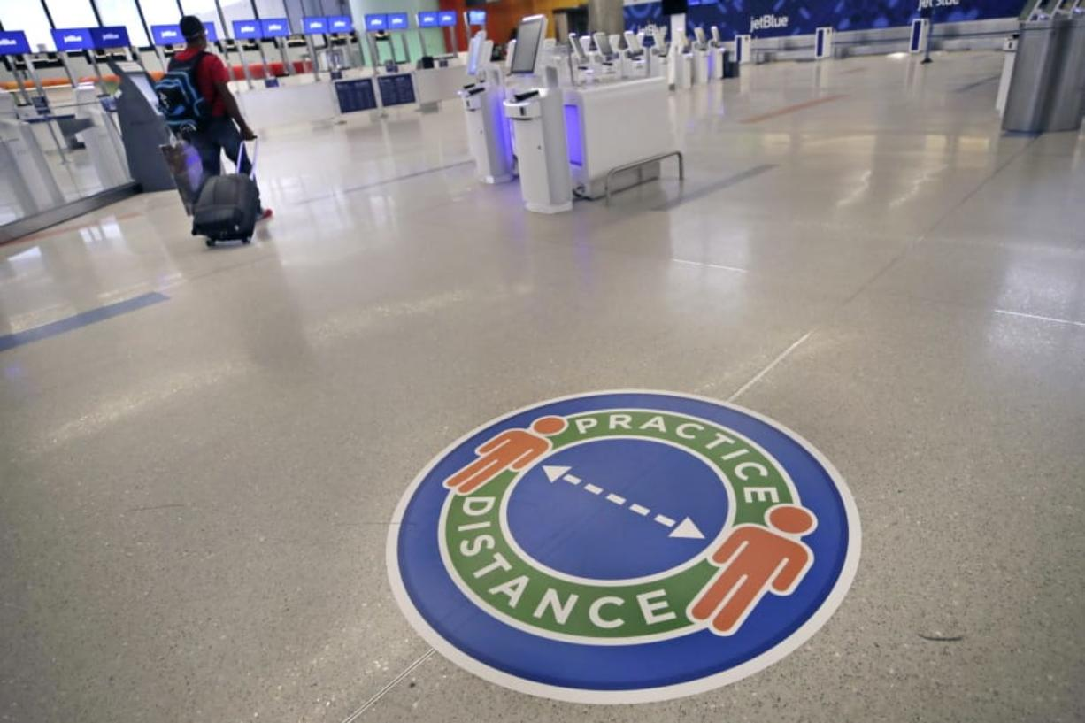 A traveler passes a sign recommending practicing social distancing, to limit spread of the coronavirus outbreak, at the nearly passenger-less JetBlue terminal at Logan Airport in Boston, Friday, May 29, 2020.