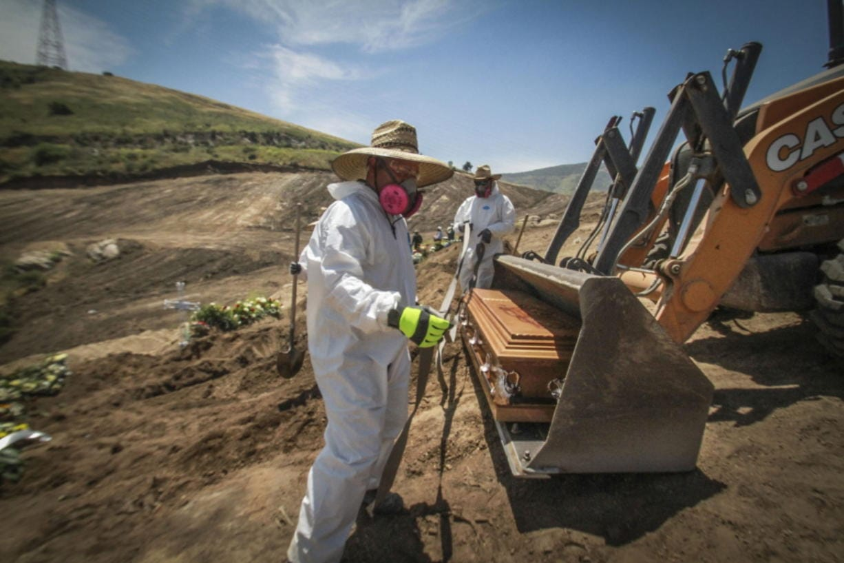 In this May 5, 2020 photo, workers in full protection gear as a precaution against the new coronavirus, unload a coffin that contain the remains of a person who died from the new coronavirus, in an area of the municipal cemetery set apart for victims of COVID-19, in Tijuana, Mexico. Citing a threat of the virus from Mexico, the Trump administration has banned hundreds of thousands of people from crossing the southern border with emergency measures that prohibit nonessential traffic and reject asylum seekers without a hearing.