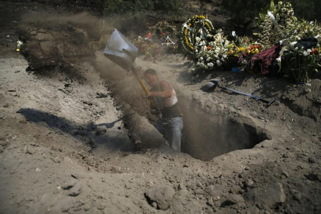 A worker digs a new grave at a newly inaugurated plot at the Valle de Chalco Municipal Cemetery, built to accommodate the rise in deaths amid the new coronavirus pandemic, on the outskirts of Mexico City, Thursday, May 21, 2020.