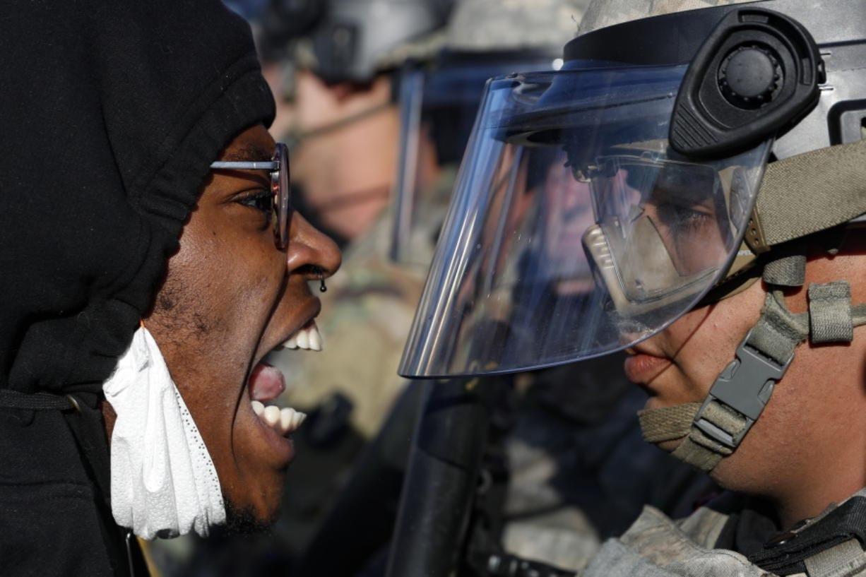 Protesters and National Guardsmen face off on East Lake Street, Friday, May 29, 2020, in St. Paul, Minn.  The massive protests sweeping across U.S. cities following the police killing of a black man in Minnesota have elevated fears of a new surge in cases of the coronavirus. Images showing thousands of screaming, unmasked protesters have sent shudders through the health community, who worry their calls for social distancing during the demonstrations are unlikely to be heard.