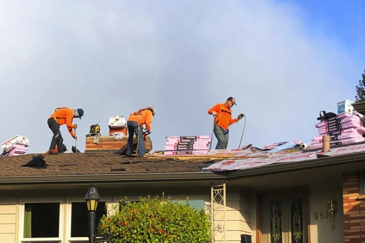 Roofers work on a home in Salem, Ore., on Tuesday. Oregon Gov. Kate Brown has allowed construction to continue under her stay-home order.