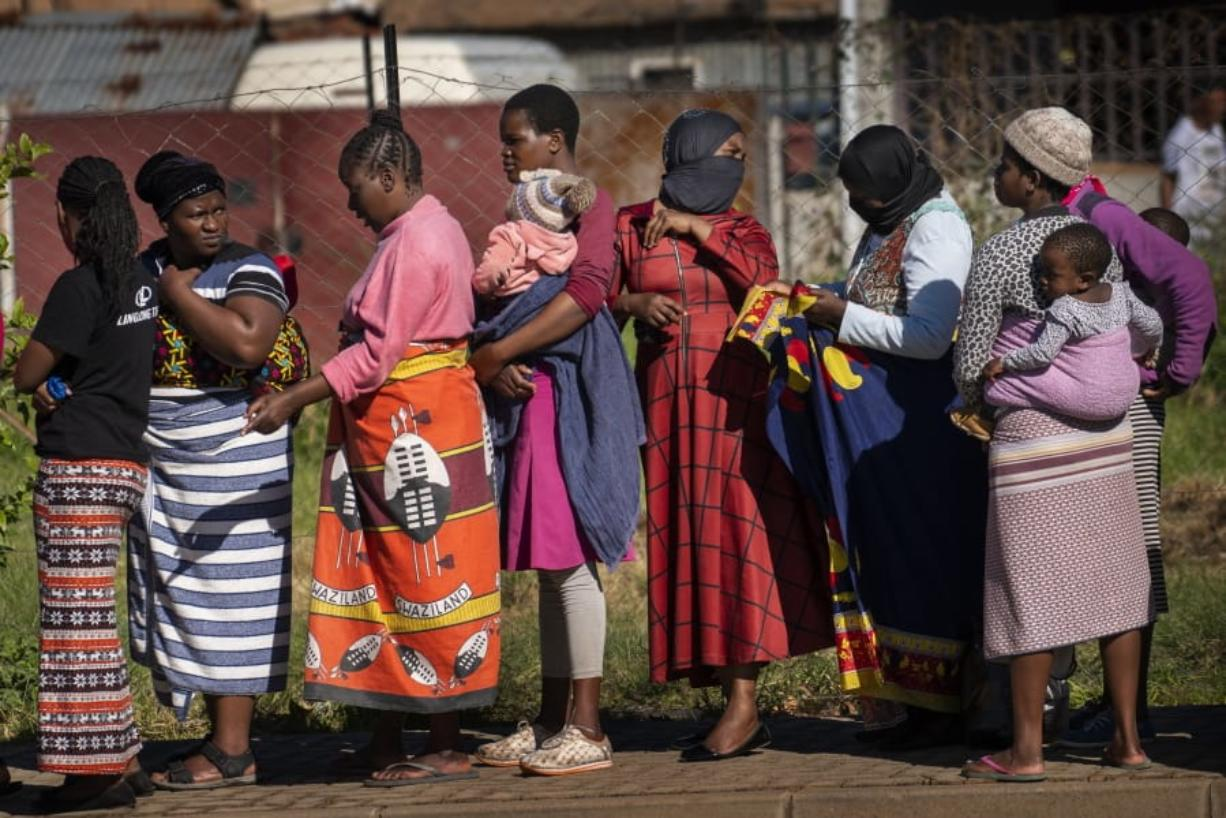 FILE- In this file photo taken Thursday, April 30, 2020, Women carrying their children lineup to receive vegetables from the Jan Hofmeyer community services in the Vrededorp neighborhood of Johannesburg. South Africa is struggling to balance its fight against the coronavirus with its dire need to resume economic activity. The country with the Africa's most developed economy also has its highest number of infections -- more than 19,000.
