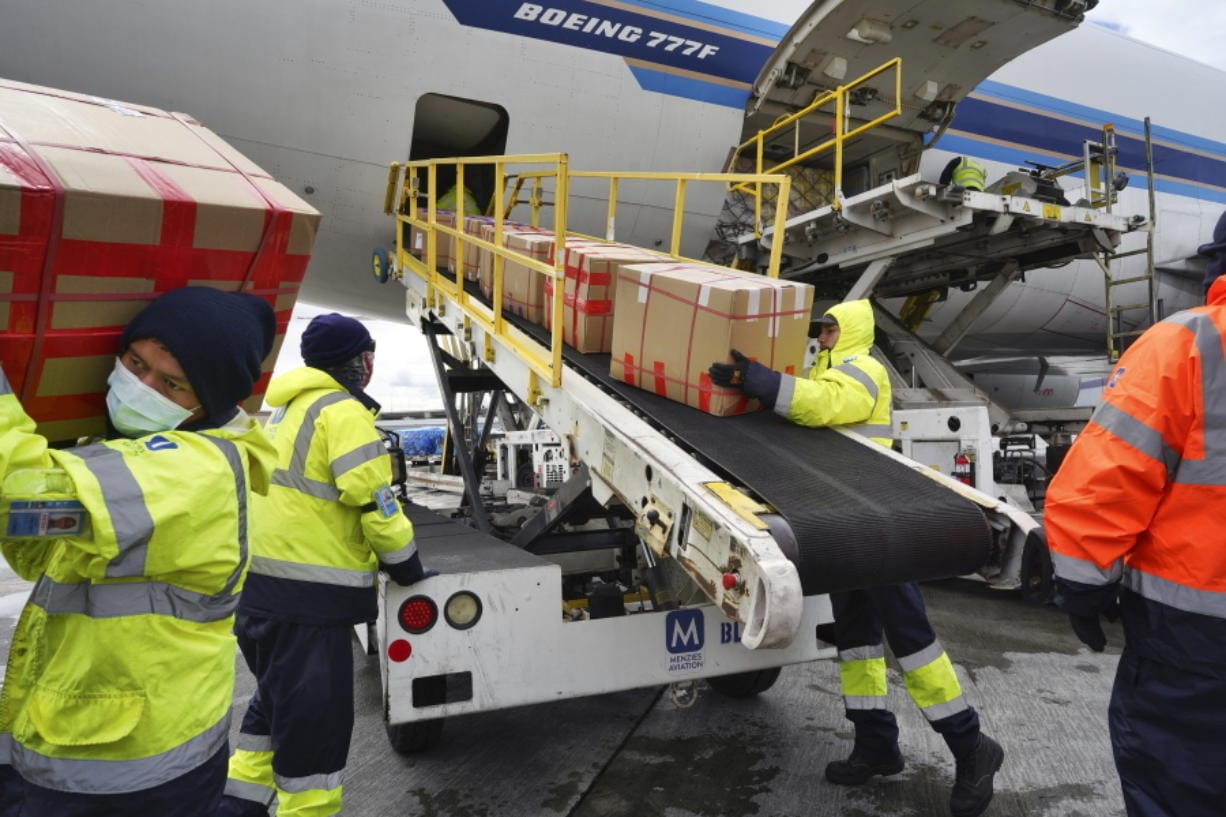 FILE - In this April 10, 2020, file photo, wearing protective masks ground crew at the Los Angeles International airport unload supplies of medical personal protective equipment, PPE, from a China Southern Cargo plane upon it's arrival. States are spending billions of dollars stocking up on medical supplies like masks and breathing machines during the coronavirus pandemic. An Associated Press survey of all 50 states found a hodgepodge of public information about the purchase of masks, gloves, gowns and other hard-to-get equipment for medical and emergency workers.