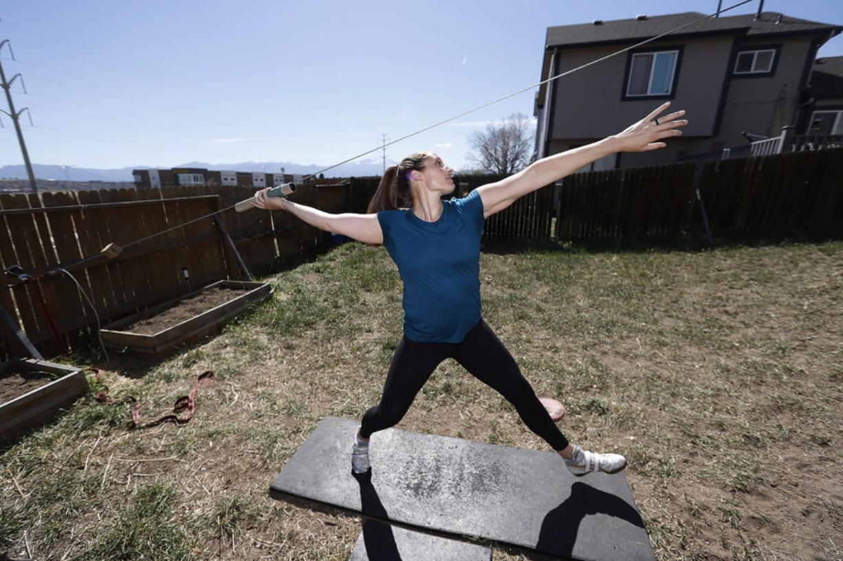 Kara Winger uses a cable system to simulate throwing a javelin as she trains outside her home in Colorado Springs, Colo., Wednesday, April 29, 2020. The renovated home of three-time Olympic javelin thrower Kara Winger now has all the training amenities she needs, including cable. No premium channels on this cable. It's just a basic wire she and her husband installed in the backyard to help her work on her technique. She throws a metal pipe along the angled cable to simulate javelin tosses.