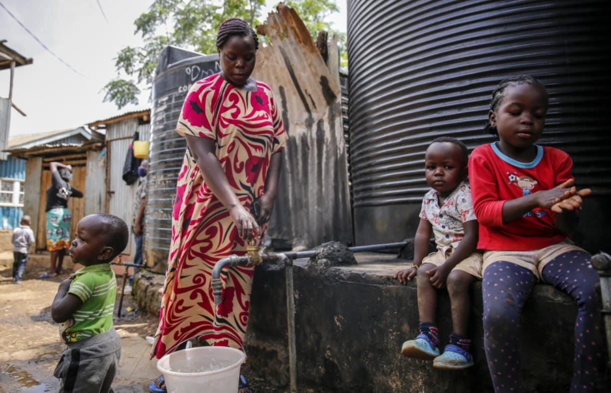 In this April 10, 2020, photo, Judith Andeka a widow and mother of five, fetches water with a bucket in the Kibera slum, or informal settlement, of Nairobi, Kenya. Andeka used to earn $2.50 to $4 a day washing clothes in Nairobi's Kibera, one of the world's biggest slums. With people not going to work because of restrictions on movement, neighbors can't afford her services.