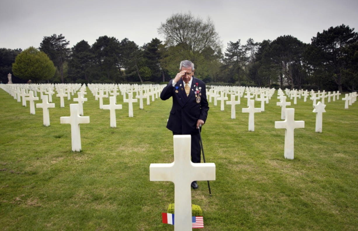 In this May 1, 2019 file photo, World War II and D-Day veteran Charles Norman Shay, from Indian Island, Maine, salutes the grave of fellow soldier Edward Morozewicz at the Normandy American Cemetery in Colleville-sur-Mer, Normandy, France. Instead of parades, remembrances, embraces and one last great hurrah for veteran soldiers who are mostly in their nineties to celebrate VE Day, it is instead a lockdown due to the coronavirus, COVID-19.