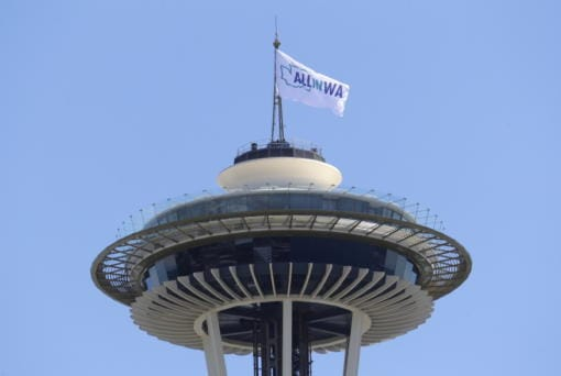 A flag promoting the All In WA relief effort flies Wednesday atop the Space Needle in Seattle. Southwest Washington is participating in the statewide campaign aimed at helping people impacted by the COVID-19 pandemic. (Ted S.